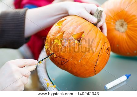 Hollowing out a scary pumpkin to prepare halloween lantern. Jack-o-lantern. Hands with knife and feld pen
