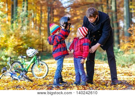 Two little kids boys and father in autumn park. Older brother and dad helping younger child to put his bike helmet. Active siblings with bicycles. Happy family