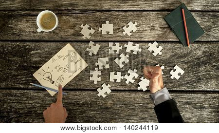 Top down view on thumb up and finger pointing to business symbols on notecard beside blank jigsaw puzzle pieces checkbook and cup over old wooden table.