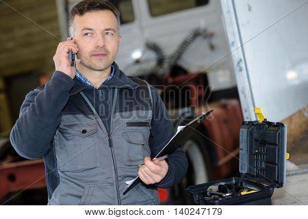 pleasant professional deliveryman holding mobile phone