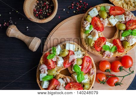 Italian appetizer Friselle. Italian dried bread Friselle with tomatoes cherry cheese mozzarella olives tuna basil and pepper in wooden pounder. Italian food. Healthy vegetarian food. Top view.
