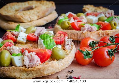 Italian appetizer Friselle. Italian dried bread Friselle on wooden board with tomatoes cherry cheese mozzarella olives tuna and basil . Italian food. Healthy vegetarian food. Selective focus.