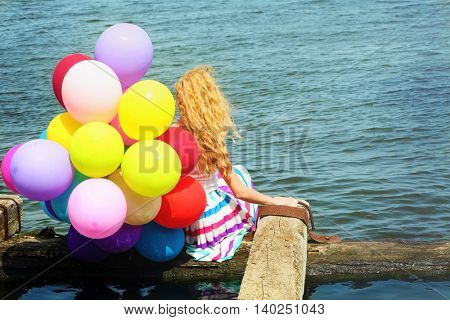 Happy woman with colorful balloons on river water background
