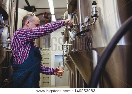 Manufacturer filling beer into glass from storage tank at brewery