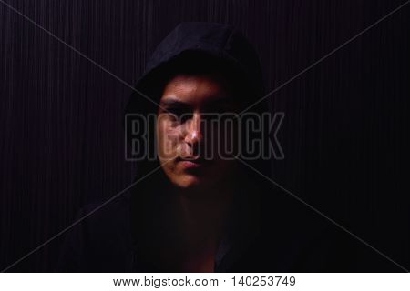 Portrait Of Teenage Boy With Serious Expression And Black Hoodie On His Head, Brown Dark Hair, Direc