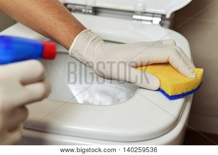 closeup of a young man cleaning a toilet with a fiber sponge and disinfectant poster