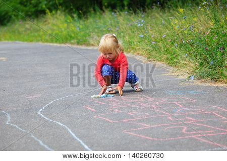 little girl drawing hopscotch on playground outdoors