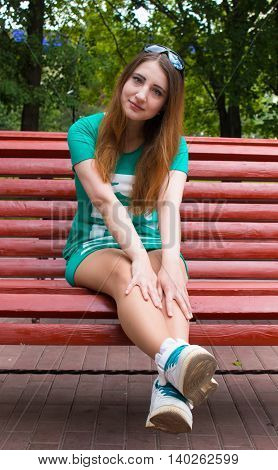 Beautiful model sits on a bench in the Park. Summer