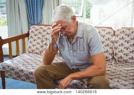 Sad senior man sitting on a couch in a retirement home
