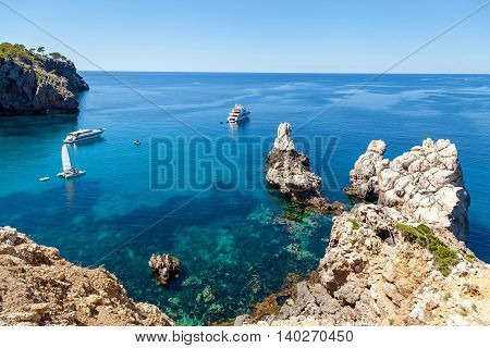 Azure bay with crystal clear water which offers incredible views of the vast expanses. Lonely sailer rock on the waves and go into the distance cruise liners. Mallorca. Spain