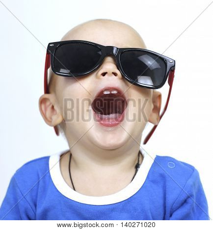 little boy the child laughs merrily in black glasses on a white background