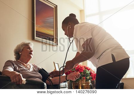 Female Doctor Measuring Blood Pressure Of Old Lady