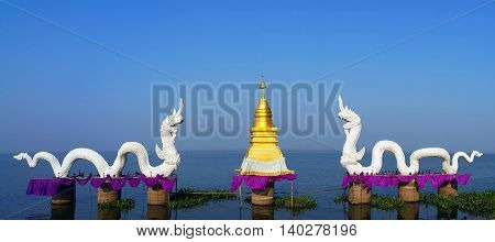 Couple of white serpent king or king of naga statues with golen stupa at Kwan phayao Thailand