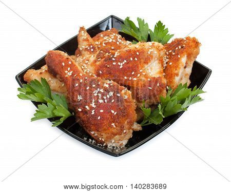 Fried Chicken Pieces Coated With Breadcrumbs And Sesame Seeds With With Parsley On A Black Plate. Is