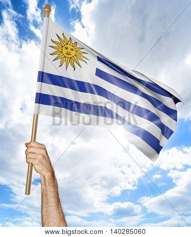 Person's hand holding the Uruguayan national flag and waving it in the sky, 3D rendering