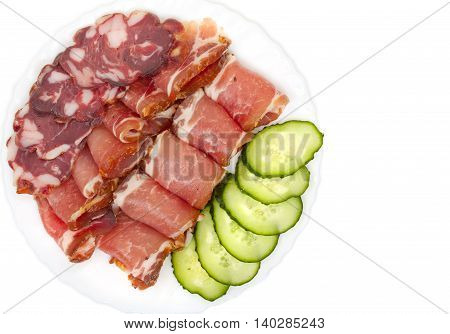 Sliced Homemade Dry Sausages And Meat Products, Cured Meat, Bacon, With Fresh Cucumber Slices On A W