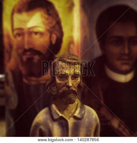 Religious Christian statue and candles of saints, Joseph, Martin, Jude - vintage instagram filtered effect