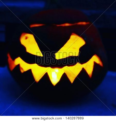 Menacing Halloween jack o lantern glowing in the night -  Instagram filter effect