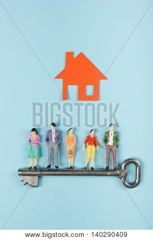 Real Estate concept. Model house, construction, house building. Paper house and people figures with key on blue background. Top view. Copy space for text