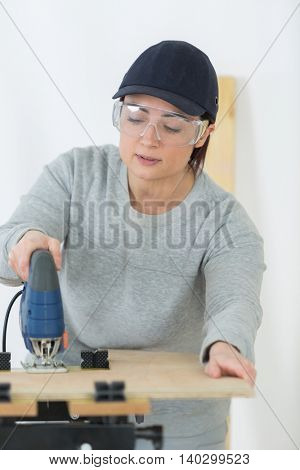 female carpenter working with a band saw