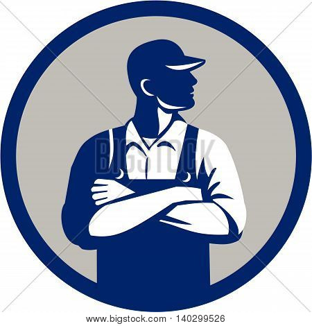 Illustration of an organic farmer wearing hat and overalls arms folded looking to the side viewed from front set inside circle on isolated background done in retro style.