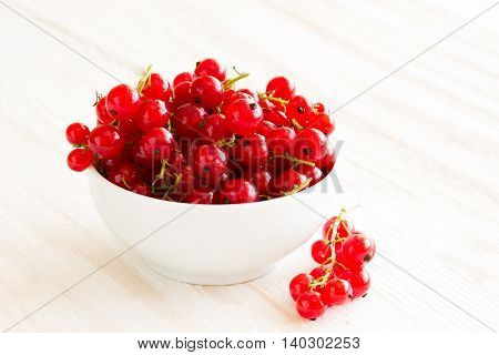 fresh sweet berry in a bowl on wooden background. redcurrants top view