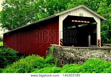 Intercourse Pennsylvania - June 4 2015: 19th century wooden Belmont Covered Bridge spans a small stream on a country road