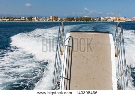 Wake and Gangway of ferry leaving harbor of Sicilian Milazzo on the way to the Aeolian islands Italy