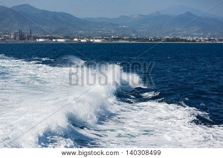 Wake of ferry leaving harbor of Sicilian Milazzo on the way to the Aeolian islands Italy