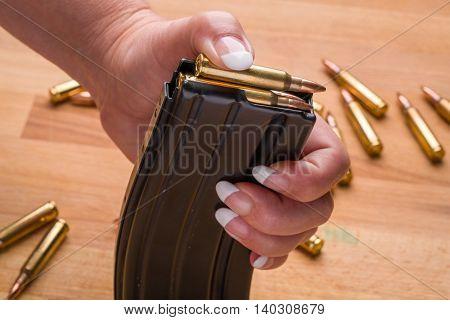 Woman Loading Ammunition in Magazine .223/556 on Wood Surface Surface