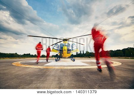 Alarm for the air rescue service. Team of rescuers (paramedic doctor and pilot) running to the helicopter on the heliport.