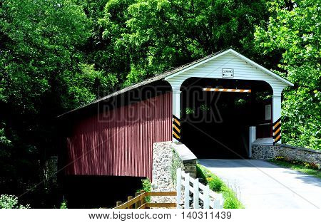 Christiana Pennsylvania - June 6 2015: 19th century Christiana Covered Bridge spans a small stream surrounded by lush verdant forests