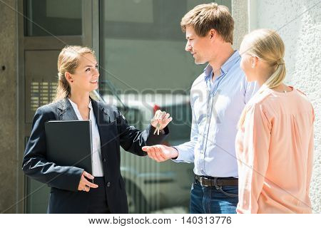 Smiling Female Real Estate Agent Giving House Key To Young Couple