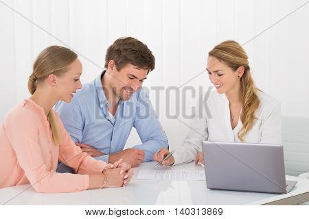 Happy Female Advisor Showing Document To Young Couple With Laptop On Desk