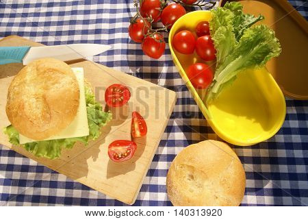 Cooking lunchbox. Homemade cheeseburger, sliced tomato on the board, knife on the board; vegetables lie in a box for lunch.