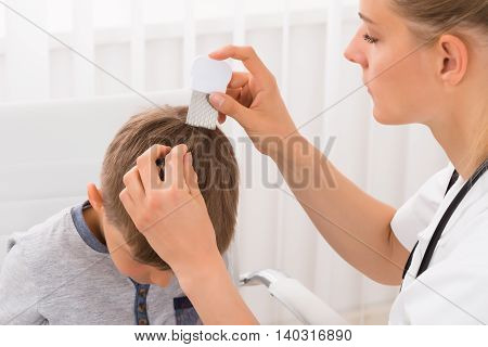 Close-up Of Female Doctor Doing Treatment On Boy's Hair With Comb