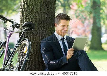 Smiling Young Male Businessman Using Digital Tablet In Park