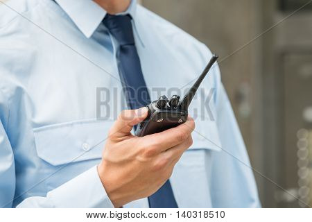 Close-up Photo Of Security Guard Holding Walkie-talkie