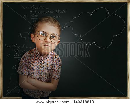 Bespectacled emotional frowning pupil boy near chalkboard