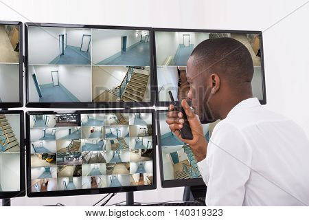 Male Operator Talking On Walkie-Talkie While Looking At CCTV Footage