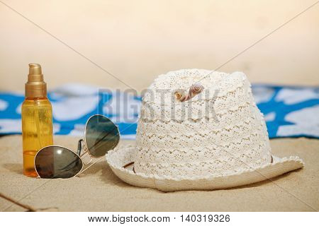 Summer vacations concept. Beach accessories. Straw hat sunglasses sun oil and blanket on sand.