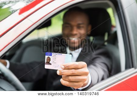 Happy Young African Businessman Showing His Driving License From Open Car Window