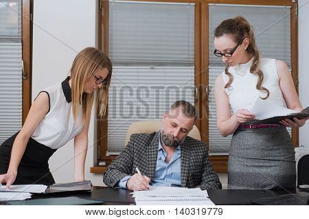 Businessman And His Assistants Secretaries In His Office.
