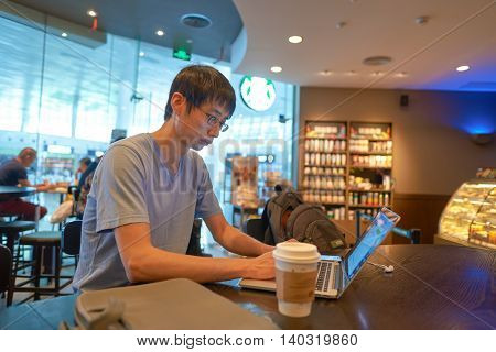 SHENZHEN, CHINA - CIRCA MAY, 2016: indoor portrait of a man at Starbucks. Starbucks Corporation is an American coffee company and coffeehouse chain.