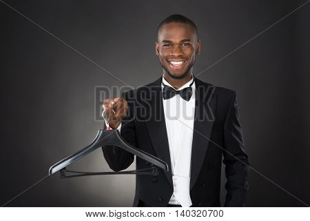 Portrait Of Happy Male Housekeeper Holding Plastic Hanger