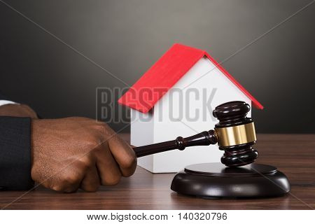 Close-up Of A Judge Hands Hitting Gavel With House Model At Desk