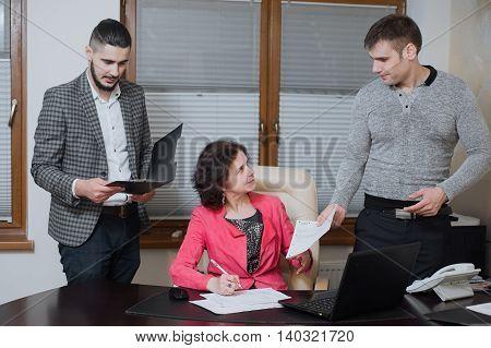 Businesswoman And His Assistants Secretaries In His Office. The Secretaries Brought The Boss Documen