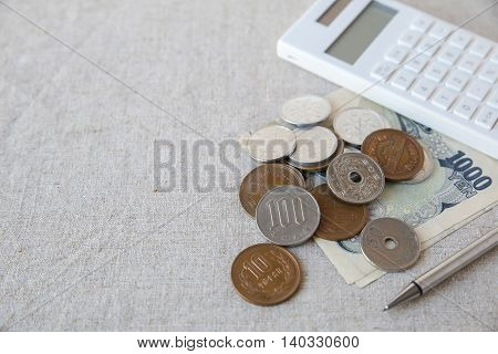 Japanese money Yens with white calculator and pen