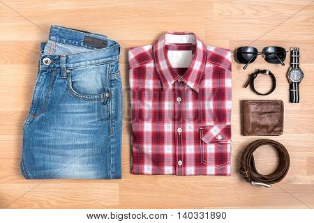 Men's casual outfits with accessories on wooden table Red plaid shirt and blue jeans with eyeglasses bracelet wallet brown belt and watch top view