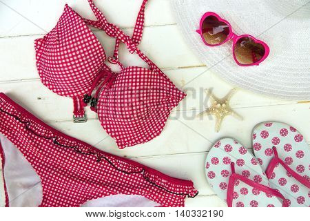 Ready to go on the beach with a red bikini, sandals, hat and heart shape sunglasses